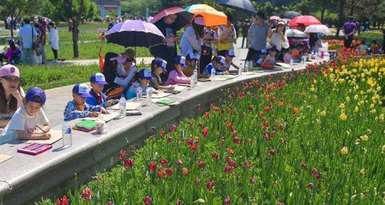活动现场,100多名孩子们拿着画笔,在画布上兴致勃勃地投入到绘画中