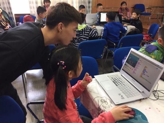 老师在帮助小朋友进行机器人体验