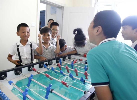 文体活动室,小学生们体验桌上足球游戏