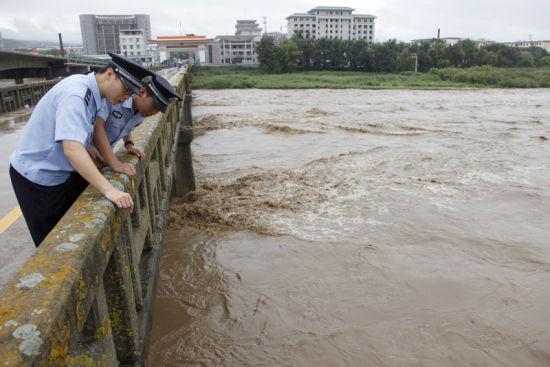 两名边检民警实时查看图们江水位和流速变化