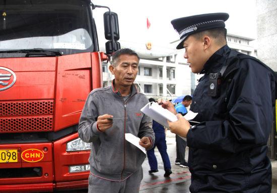 一名边检民警为出境货车司机办理通关手续