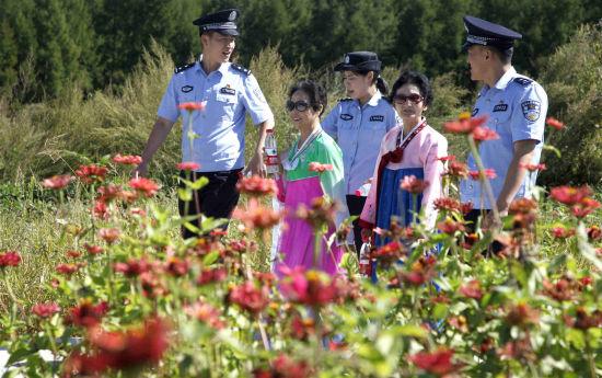 12日,边检民警陪朝鲜族阿迈(大娘)畅游花海
