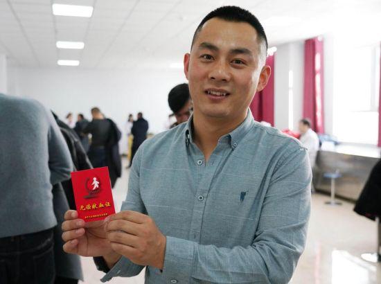 """镇赉县运输管理所林波拿到献血证很开心,说""""献血能挽救生命,这是一件很有意义的事。""""潘晟昱 摄"""