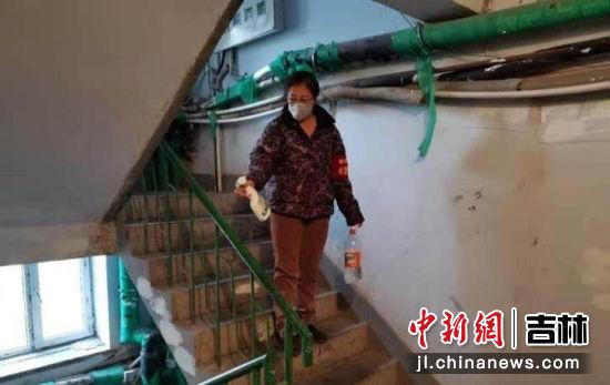 图为电力社区楼道消杀志愿者对楼道进行消杀