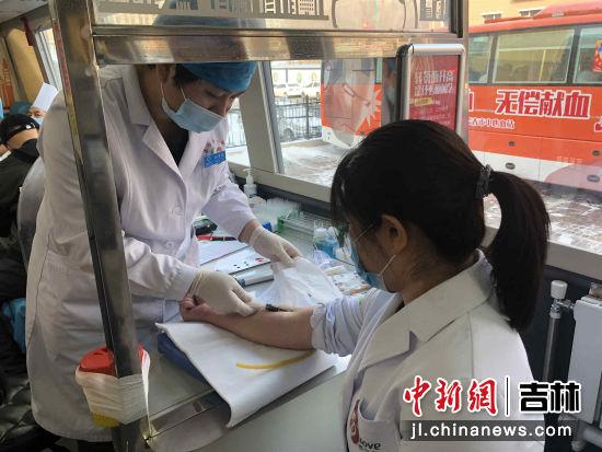 图为医生正在进行献血