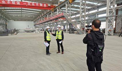 向媒体记者介绍中国二十二冶遵化装配式建筑生产基地二期车间自主研发的PC生产线