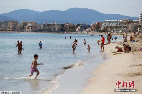当地时间5月25日,民众在西班牙大加那利岛重新开放的海滩上玩乐休闲。据报道,随着疫情缓解,西班牙逐步放宽限制措施,一些省份放宽了解封第二阶段的一些限制。