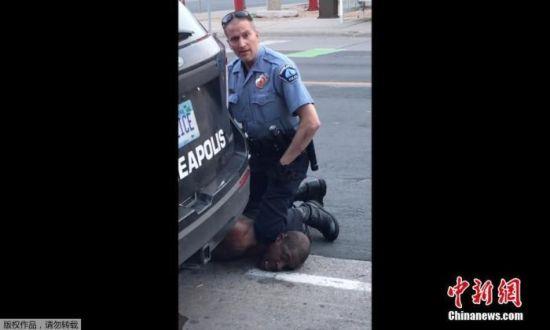 当地时间5月25日,美国明尼苏达州明尼阿波利斯市一名警察在逮捕非裔男子乔治・弗洛伊德时,将其按在地上,用膝盖顶住脖子。(视频截图)