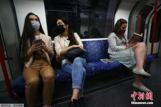 当地时间6月15日,英国伦敦,乘客戴口罩乘坐地铁出行。