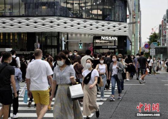 图为日本当地民众佩戴口罩走过东京街头。 中新社记者 吕少威 摄