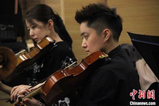 西安交响乐团中提琴演奏员庄��(右)在排练厅彩排。 张一辰 摄