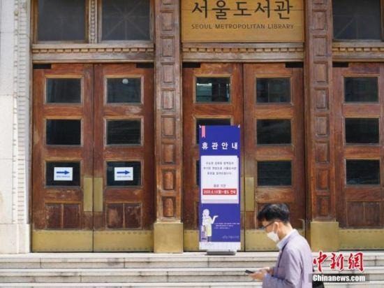 6月23日,一位韩国首尔市民经过首尔市立图书馆门前,该图书馆贴出闭馆通知。近来,包括韩国首尔、仁川、京畿道在内的首都圈确诊病例持续增加。 中新社记者 曾鼐 摄