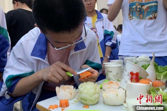 学生利用细胞吸水和失水的原理,先将萝卜失水,做好造型后,再放入清水中吸水,使萝卜花不再易碎,得以更好定型。 李佩珊 摄
