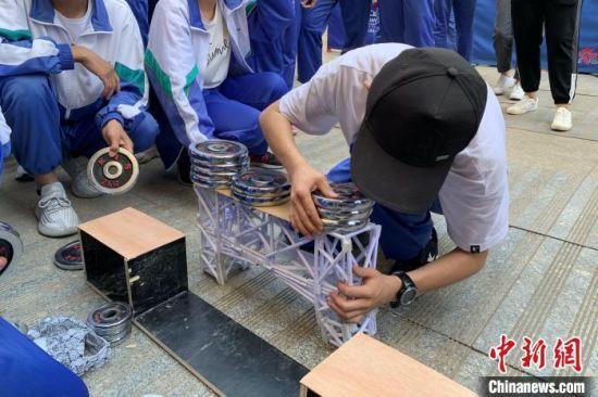 学生用哑铃测量自制纸桥的承重能力。 李佩珊 摄