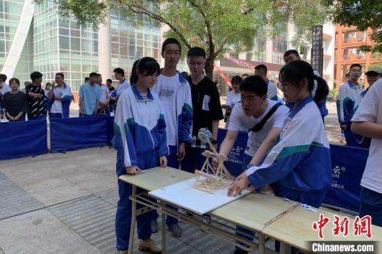 学生使用一次性竹筷搭建投石机进行投石比赛。 李佩珊 摄