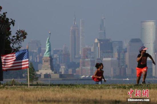当地时间7月4日,两名孩童在纽约曼哈顿对岸的海滨草坪上奔跑,当日是美国独立日。中新社记者 廖攀 摄
