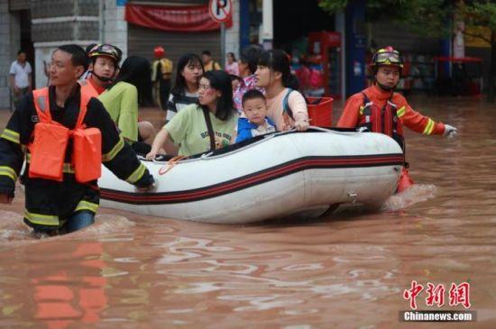 资料图:消防救援人员紧急转移被困民众。 肖乐峰 摄