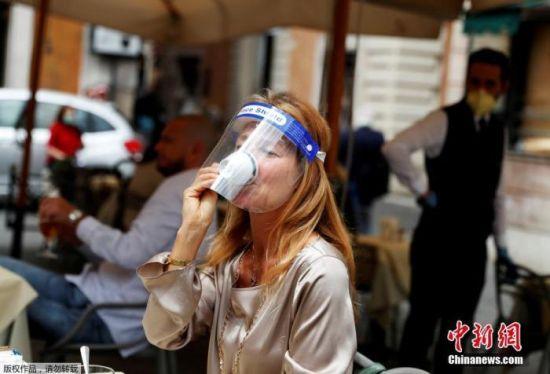 资料图:戴面罩的女士在意大利罗马街头喝咖啡。