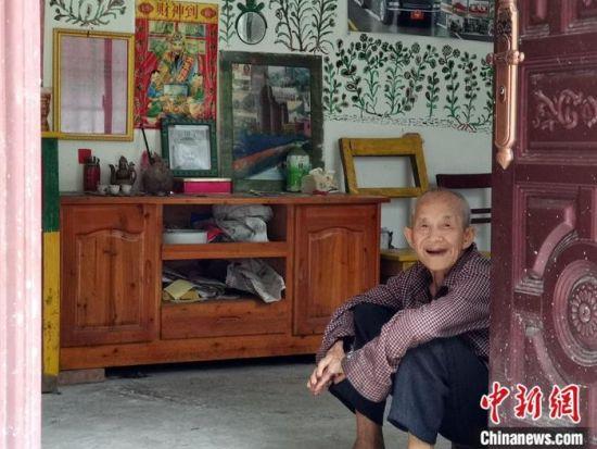 谭运日老人坐在新家门口对客人微笑。蒋雪林 摄