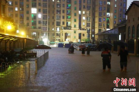图为江西南昌一小区道路积水严重,民众涉水前行。 刘占昆 摄