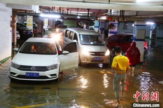 因暴雨倒灌车库,车主把车辆开出受淹的地下车库。 刘占昆 摄