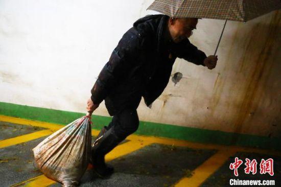 图为社区工作人员正提着沙袋去封堵灌入车库的积水。 刘占昆 摄