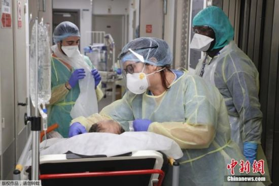 当地时间4月8日,巴黎附近的巴尼奥莱市一家医院内,医护人员在送新冠肺炎患者扫描检查的途中进行护理。