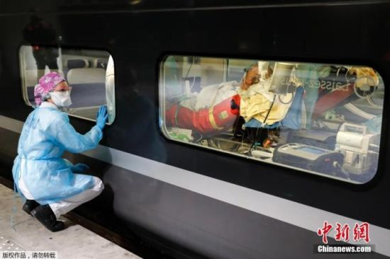当地时间4月1日,在法国巴黎Gare d'Austerlitz火车站,医务人员透过列车窗户观察高速列车内的患者。