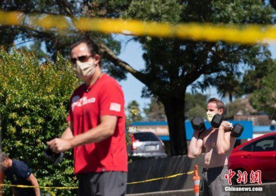 """当地时间6月20日,美国加利福尼亚州马林县圣安塞尔莫一家健身房在门口的道路上重新营业,民众在保持""""社交距离""""的前提下健身。"""