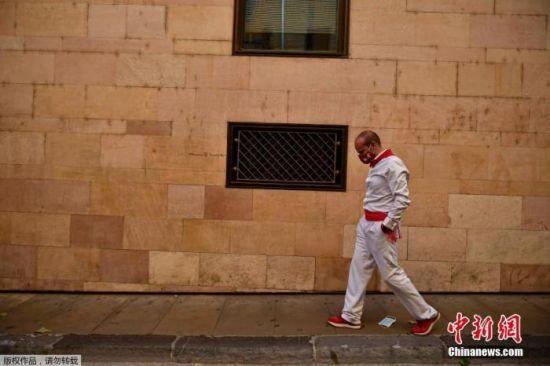 资料图:当地时间2020年7月7日,西班牙北部班普罗纳,今年的奔牛节被取消,一位戴着面罩的参赛者沿着圣佛明节奔牛的路线行走。
