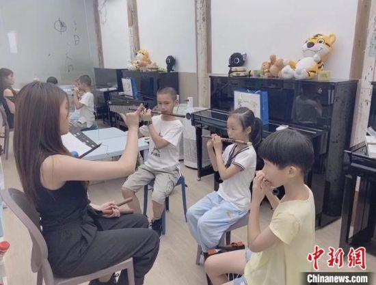 来自台北的云响艺术机构竹笛教师柯承�u(左一)教授长笛。 林春茵 摄