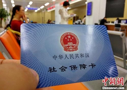 资料图:某市民服务中心前来办理社保业务的民众展示自己的社会保障卡。 中新社记者 张斌 摄