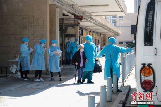 7月24日下午,大批身穿防护装备的医护人员,到位于香港大围隆亨�荣心楼的救世军隆亨长者之家撤走院内长者。 中新社记者 秦楼月 摄