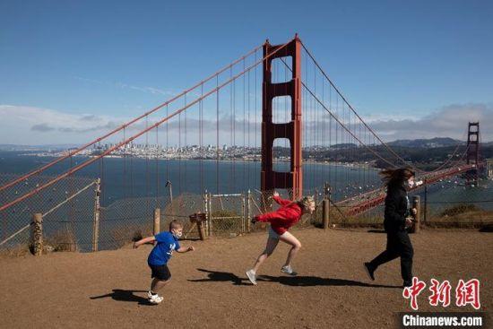 资料图:当地时间7月21日,游客在美国加州旧金山金门大桥附近游玩。中新社记者 刘关关 摄