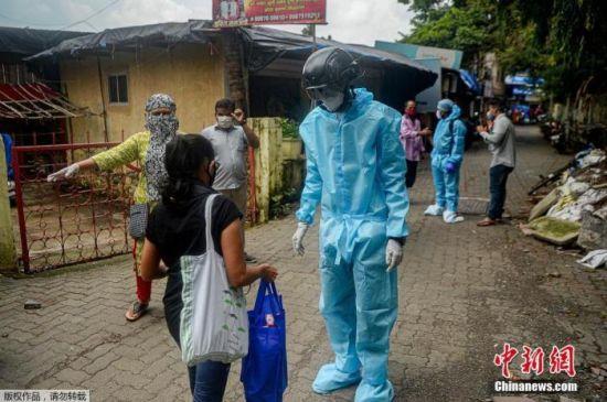 资料图:当地时间2020年7月21日,印度孟买,一名非政府组织的卫生工作志愿者穿着防护衣,戴着装有热扫描传感器的智能头盔在居民区挨户查看居民体温。