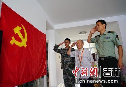 """7月28日,98岁的吉林省镇赉县参战老兵张旭与县人武部官兵一起向党旗敬军礼,庆祝第93个""""八一""""建军节。老兵张旭1949年入党,党龄70年。潘晟昱/供图"""