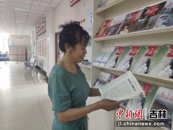 65岁的周云霞在社区看杂志打发时间。谭伟旗/供图