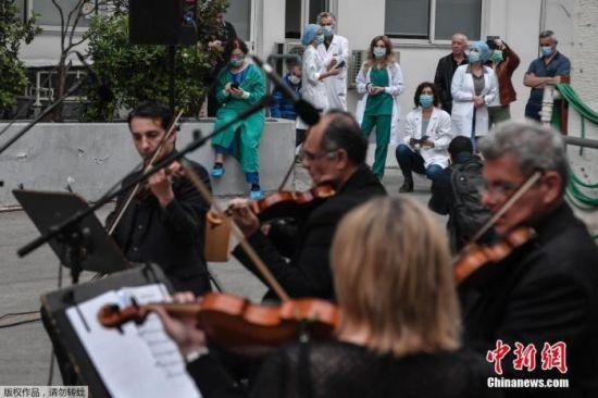当地时间4月20日,新冠疫情期间,希腊雅典福音医院的医务人员在院子里聆听希腊国家广播交响乐团的音乐会。