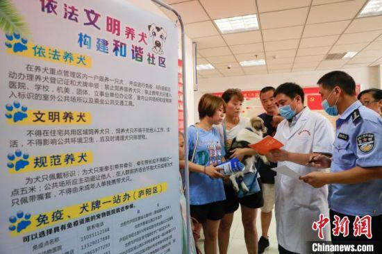社区工作人员和民警开展文明养犬宣传。 赵明 摄