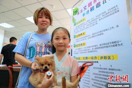 社区居民带着犬只前来登记办理养犬证。 赵明 摄