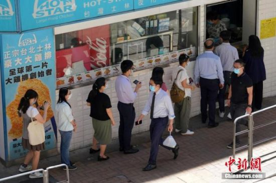 资料图:众多打工者在香港湾仔一家餐厅门口排队购买外卖餐食。中新社记者 张炜 摄