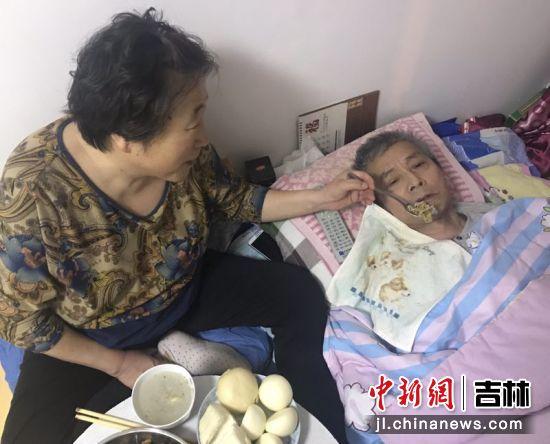 贺春菊在给丈夫喂饭。受访者/供图
