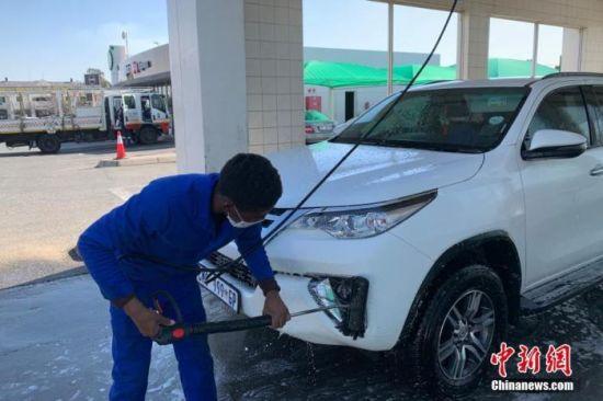 当地时间7月22日,南非约翰内斯堡,一家洗车店的员工佩戴口罩为顾客清洗车辆。 中新社记者 王曦 摄