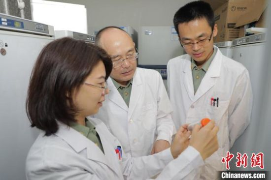 军事科学院军事医学研究院曹务春研究员(中)与团队科研人员正在观察试验活蜱。 张振威 摄