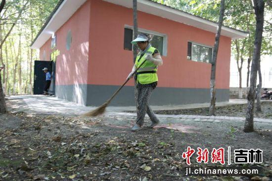环卫工人拿着扫帚清扫落叶。王晓彤/供图