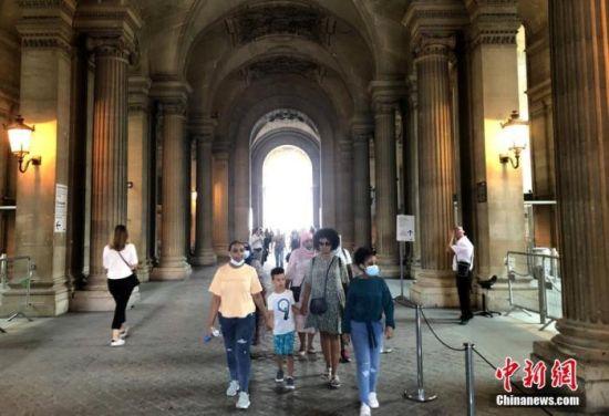"""当地时间8月14日,巴黎被法国官方列为新冠病毒传播""""高风险地区""""。图为当天在卢浮宫外的民众,其中一些人仍未戴口罩。中新社记者 李洋 摄"""