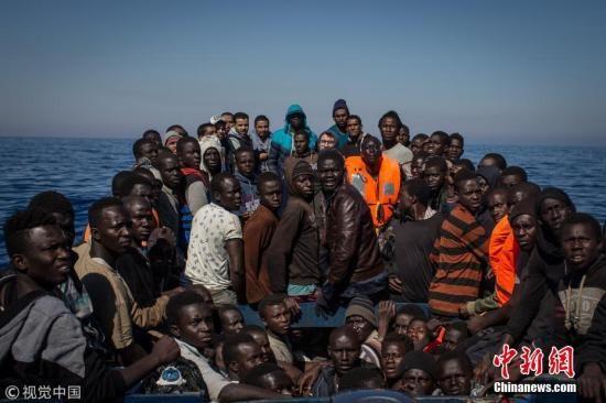 资料图:当地时间2017年5月18日,意大利兰佩杜萨,移民和难民挤在一艘小木船上等待救援。 Chris McGrath 摄 图片来源:视觉中国