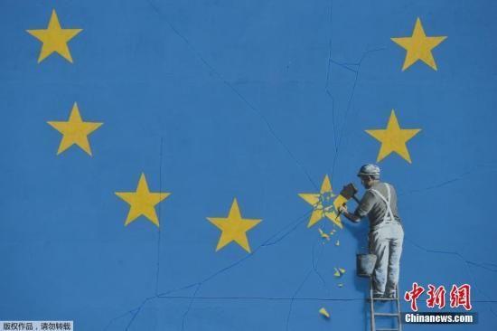 资料图:当地时间2017年5月7日,英国多佛,一名街头艺术家班克西创作了一幅画,画面中一名工人正从欧盟12星旗帜上抹掉一颗星,寓意着英国将脱离欧盟。