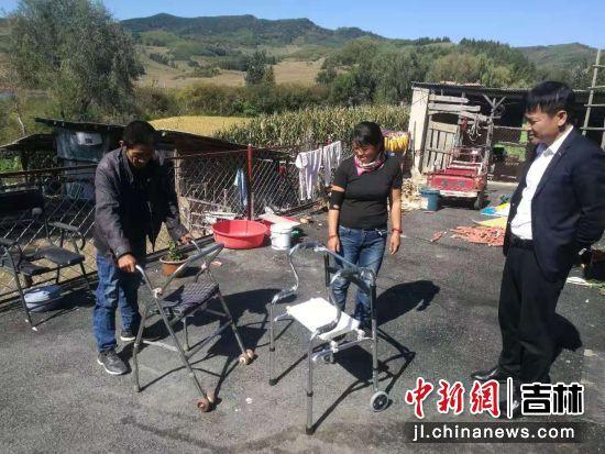 柳河县残联干部到贫困残疾户李德友家中发放助行器/吉林省残联供图