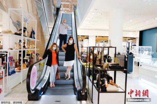 图为在巴黎的一家商店里,顾客戴着口罩进入。